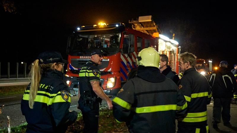 Brandweerlieden en agenten staan in het donker bij een brandweerauto