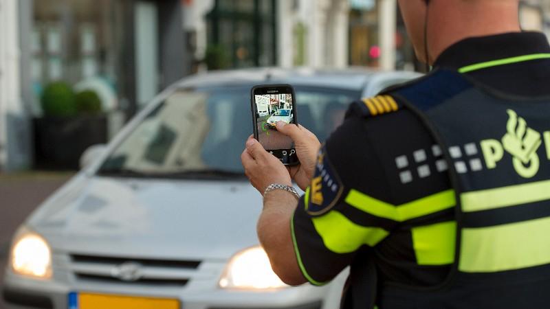 Agent fotografeert kenteken auto met meos